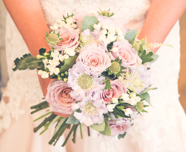 Bride holding a pink, yellow and white rose bouquet. Beautiful wedding flowers and arrangements by Willow and Blooms