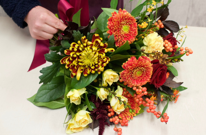 Wrapping a bouquet with orange, red and yellow shades. Flowers in Newbury by Willow and Blooms.