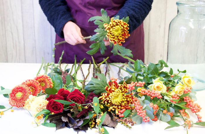 Making a bouquet with yellow, red and orange flowers. Flowers being sorted by colour and size. Flowers in Newbury by Willow and Blooms.